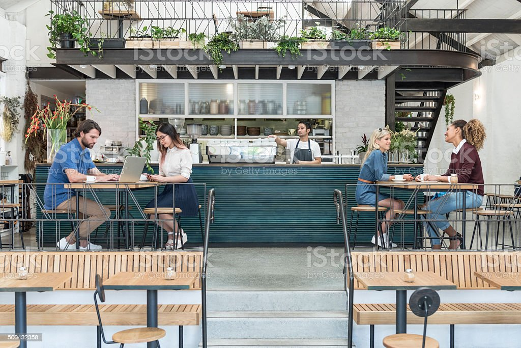 Customers in modern cafe with drinks and laptop stock photo