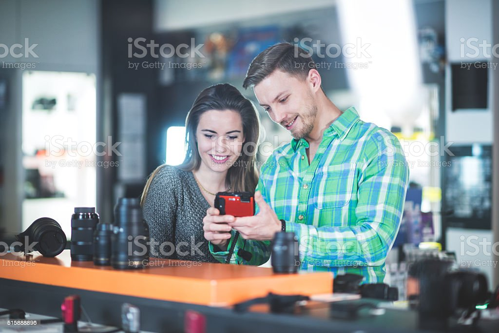 Customers in the store looking at digital camera stock photo