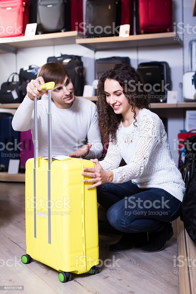 customers looking at roll-aboard bags in store stock photo