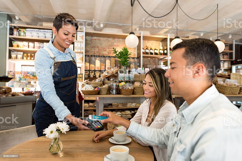 Customers making a contactless payment at a restaurant stock photo