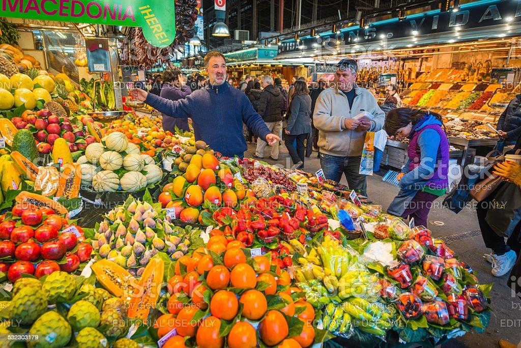 Customers shopping at colourful market stall La Boqueria Barcelona Spain stock photo