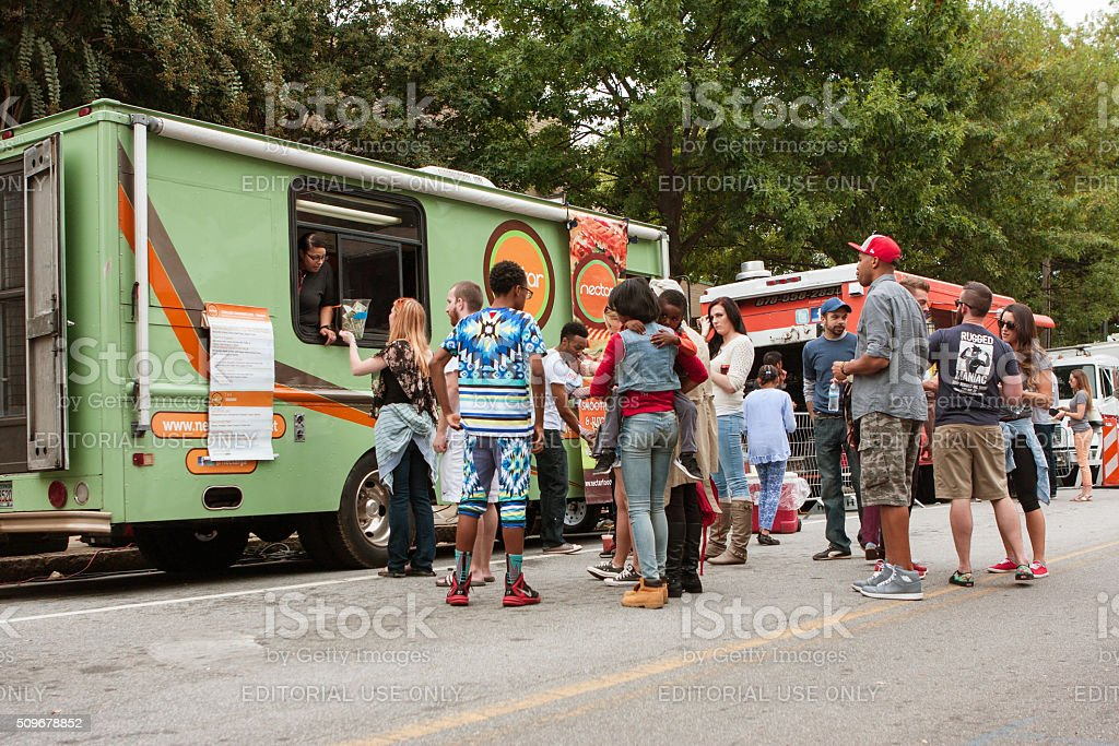 Customers Stand In Line To Buy Meals From Food Trucks stock photo