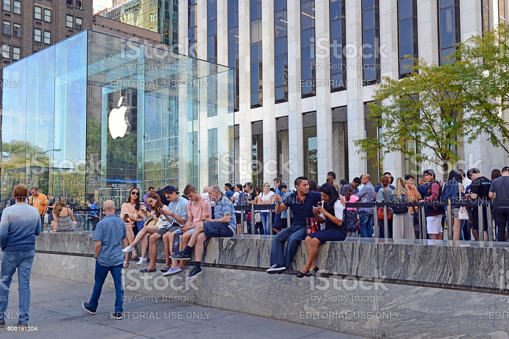 Customers wait on long lines outside the Apple Store stock photo