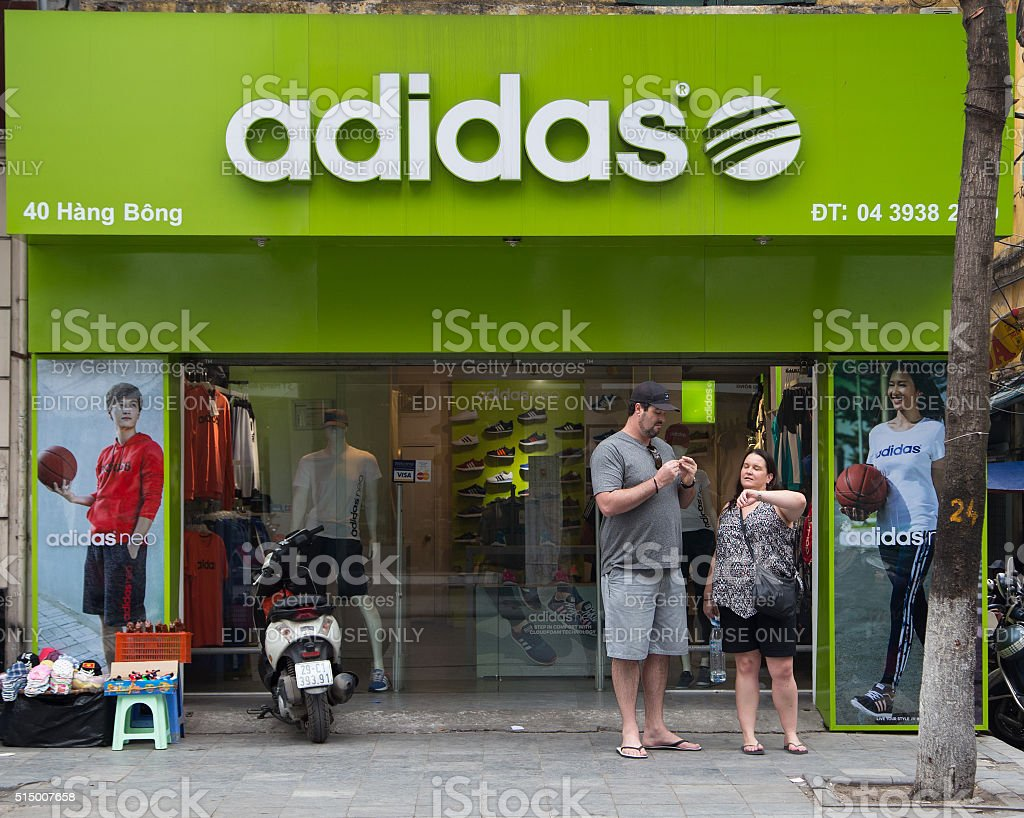 Customers walk out of a store selling Adidas product stock photo