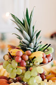 Cut ananas and other fruits stand served on steel dish