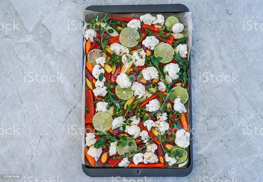 Cut assorted vegetables on baking sheet stock photo