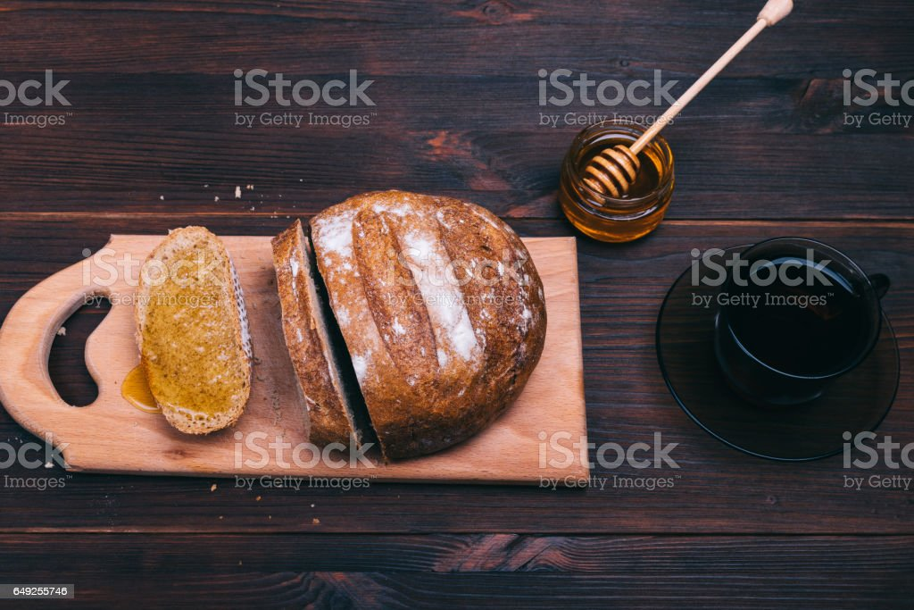 Cut bread, honey and a cup of tea on a brown table stock photo
