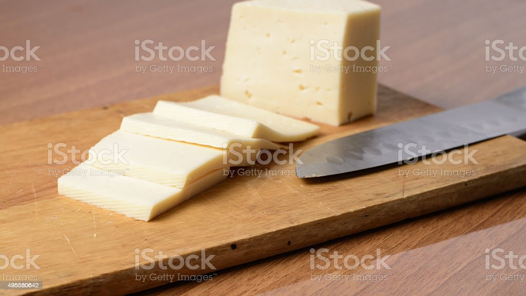 Cut cheese on a wooden board stock photo