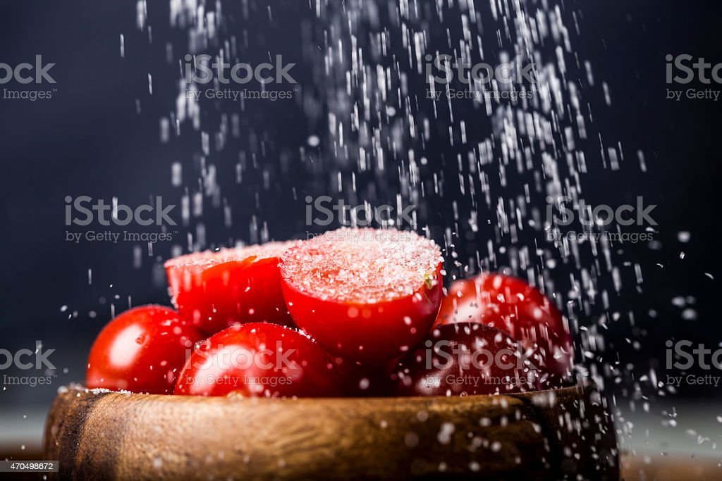 Cut Cherry Tomato with Salt Seasoning in a wooden bowl stock photo