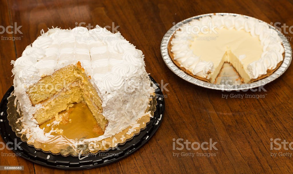 Cut Coconut Cake and Lemon Meringue Pie on Wood Table stock photo