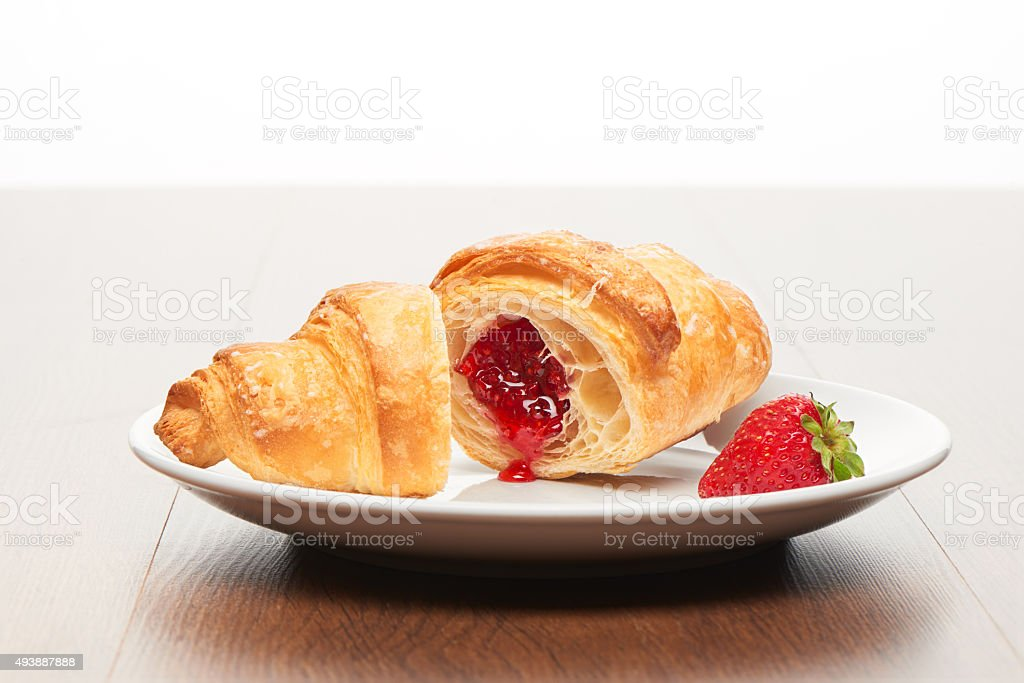 Cut croissant with strawberry jam filling, strawberry on white plate stock photo