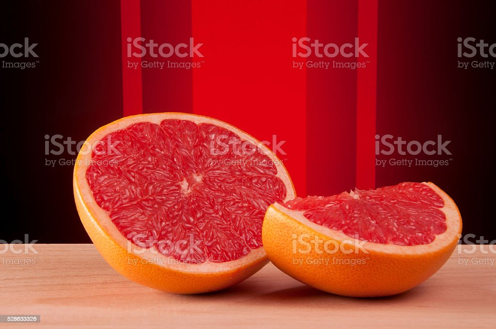 Cut grapefruit on the black and red abstract background stock photo
