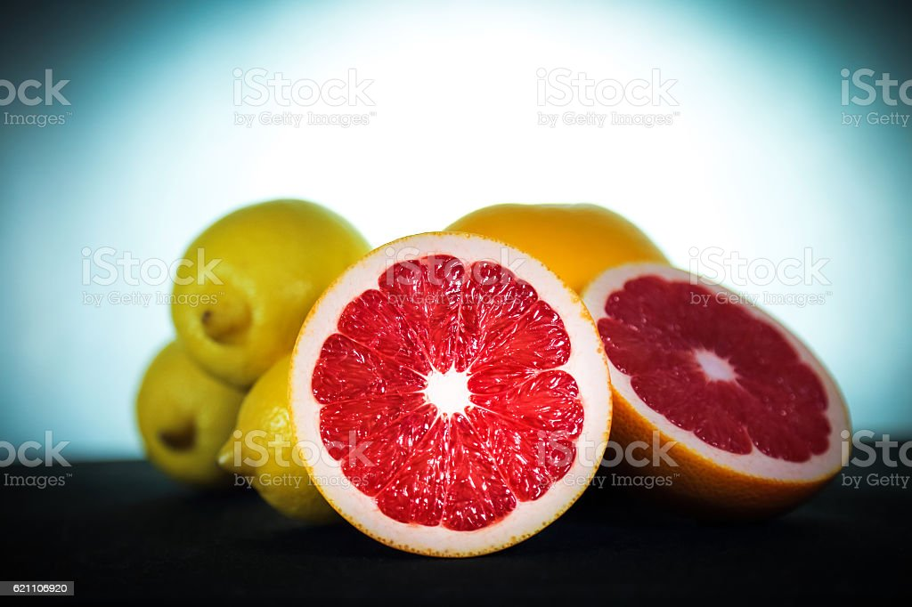 Cut grapefruits and lemons on black surface, light in backgrond stock photo