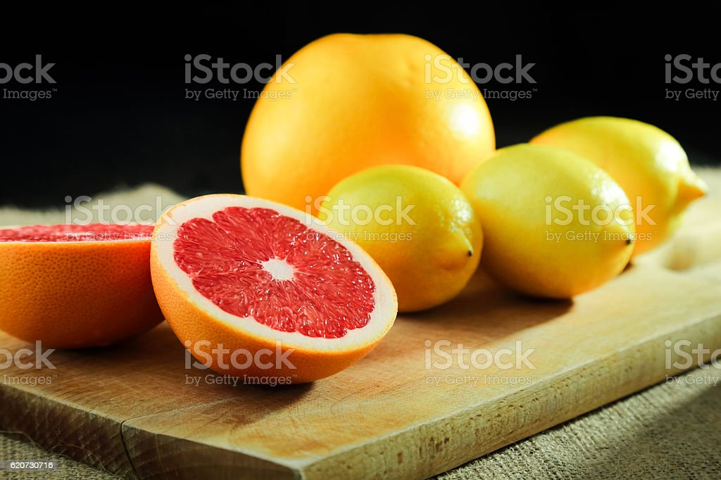 Cut grapefruits and lemons on wooden cutting board, dark backgrond stock photo