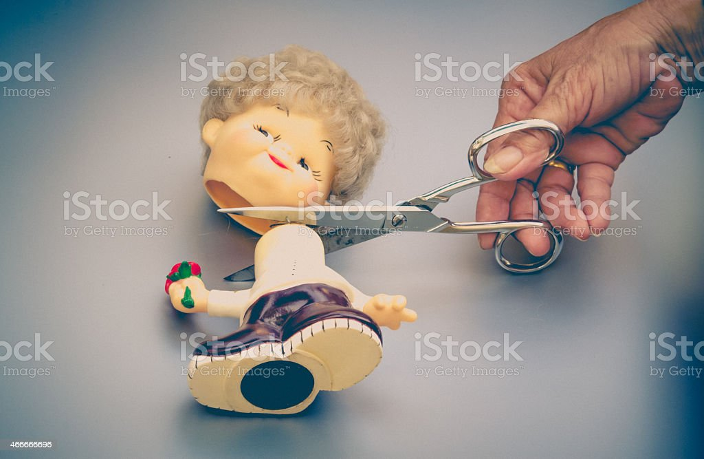 cut head  doll with scissors stock photo