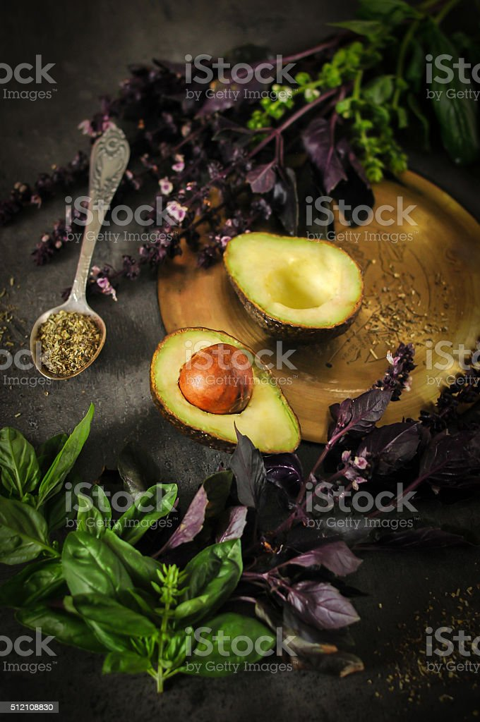 Cut in half avocado with spices and herbs stock photo