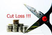 Cut Loss or stop loss concept the scissors cut a coins
