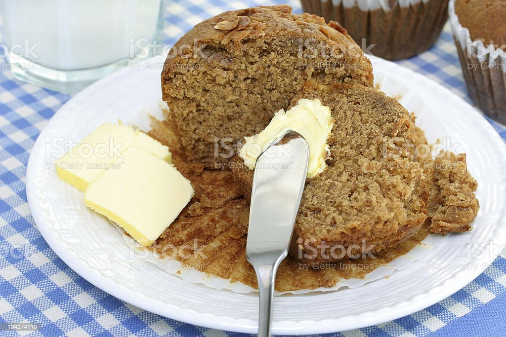 Cut oat bran muffin with butter and milk. stock photo