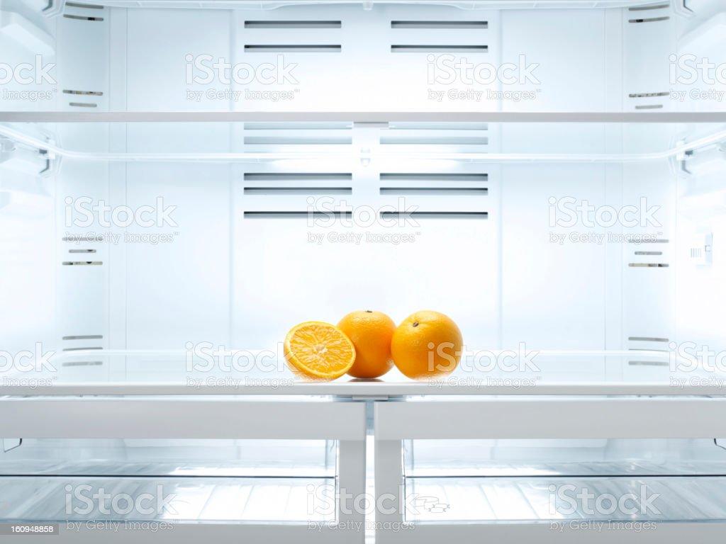 cut open orange in refrigerator stock photo