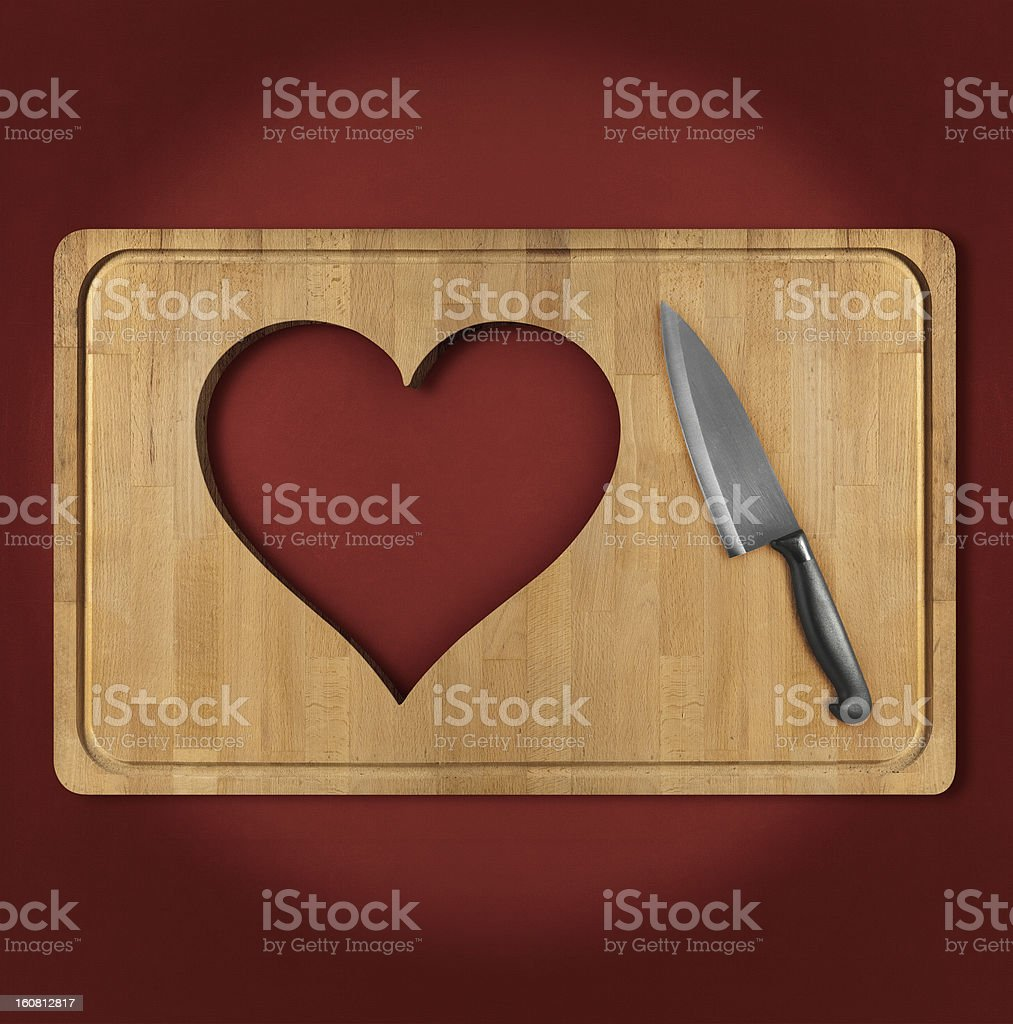 Cut out heart shape on wooden cutting board royalty-free stock photo