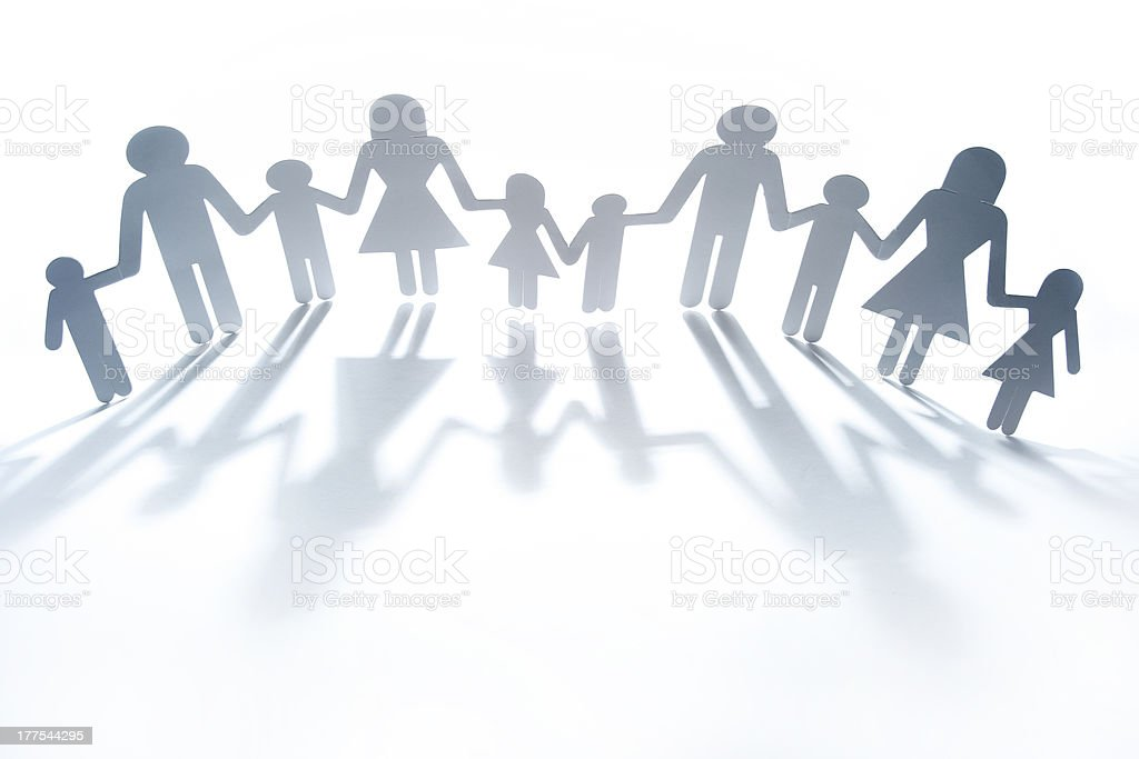 Cut out paper dolls holding hands against white background stock photo