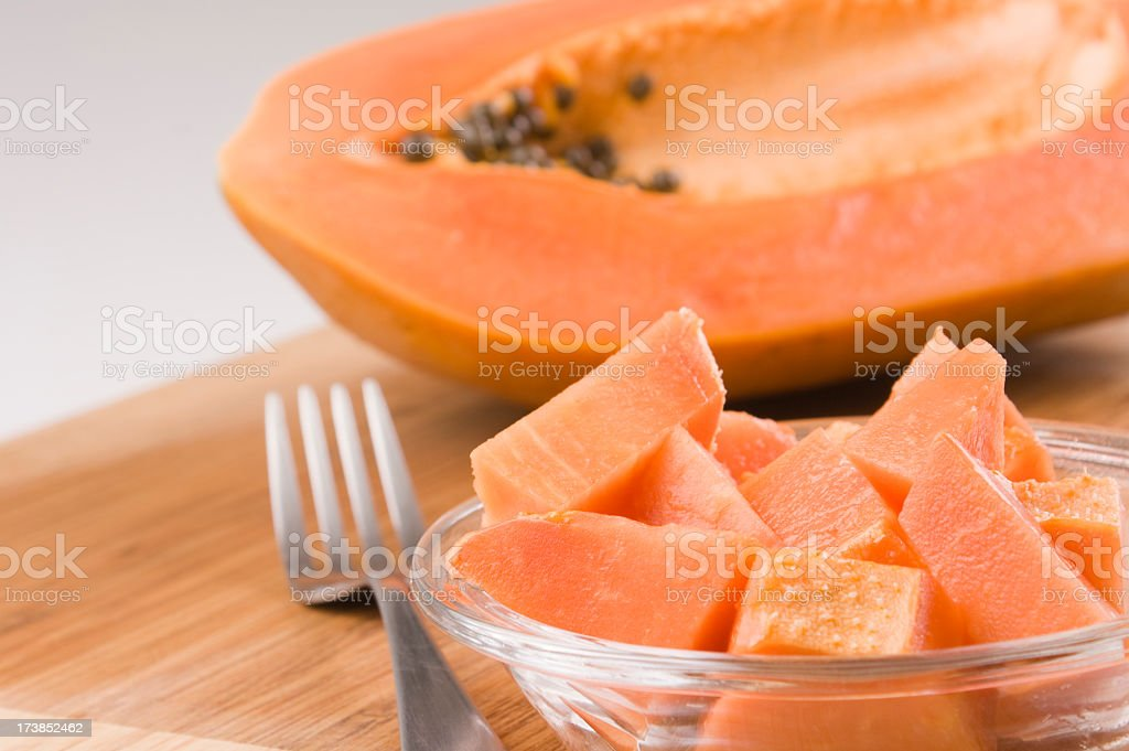 Cut papaya on a wooden board with a silver fork stock photo