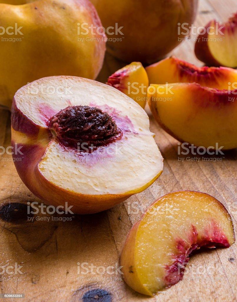cut peach on wooden table stock photo