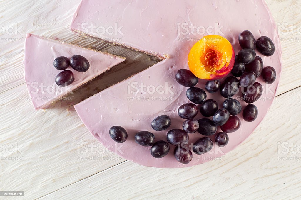 Cut piece fruit cheesecake decorated with grapes stock photo