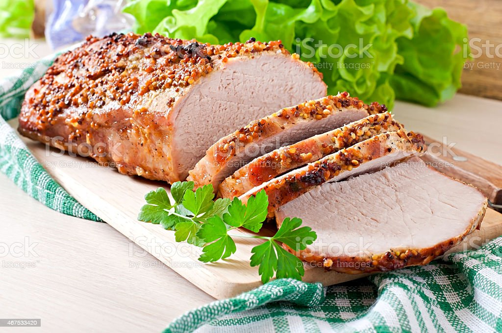 Cut pieces of baked meat on the table stock photo