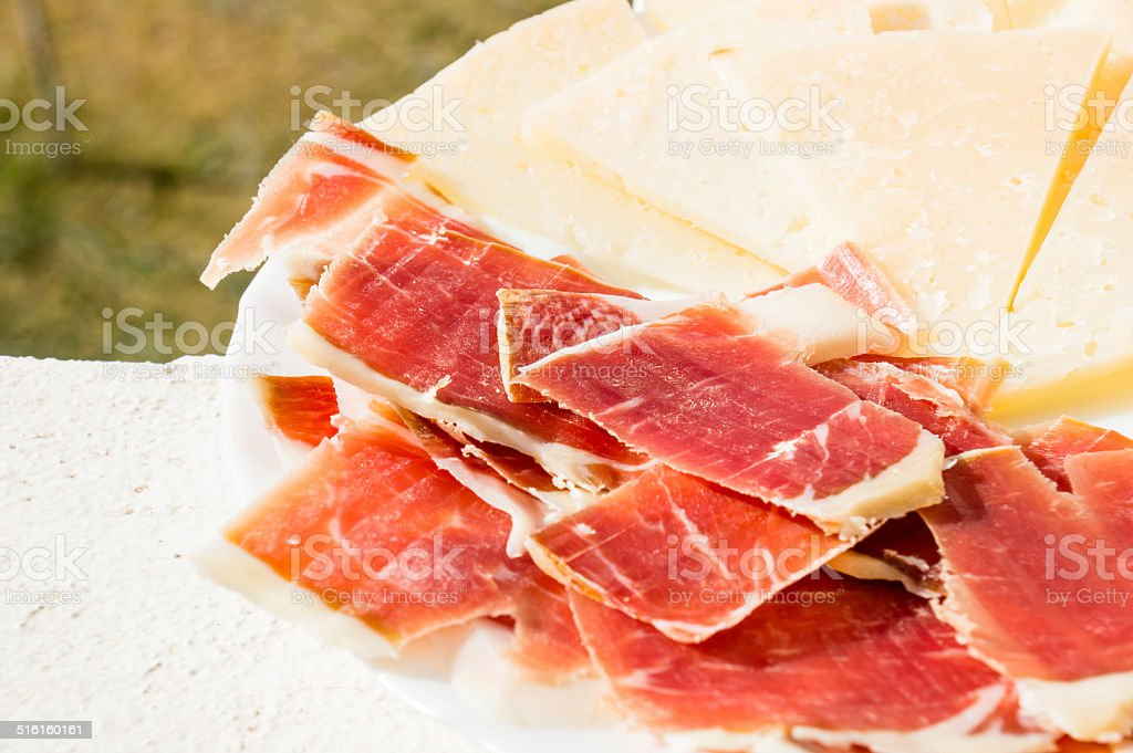 cut slices of ham (panish jamon iberico) and cheese stock photo