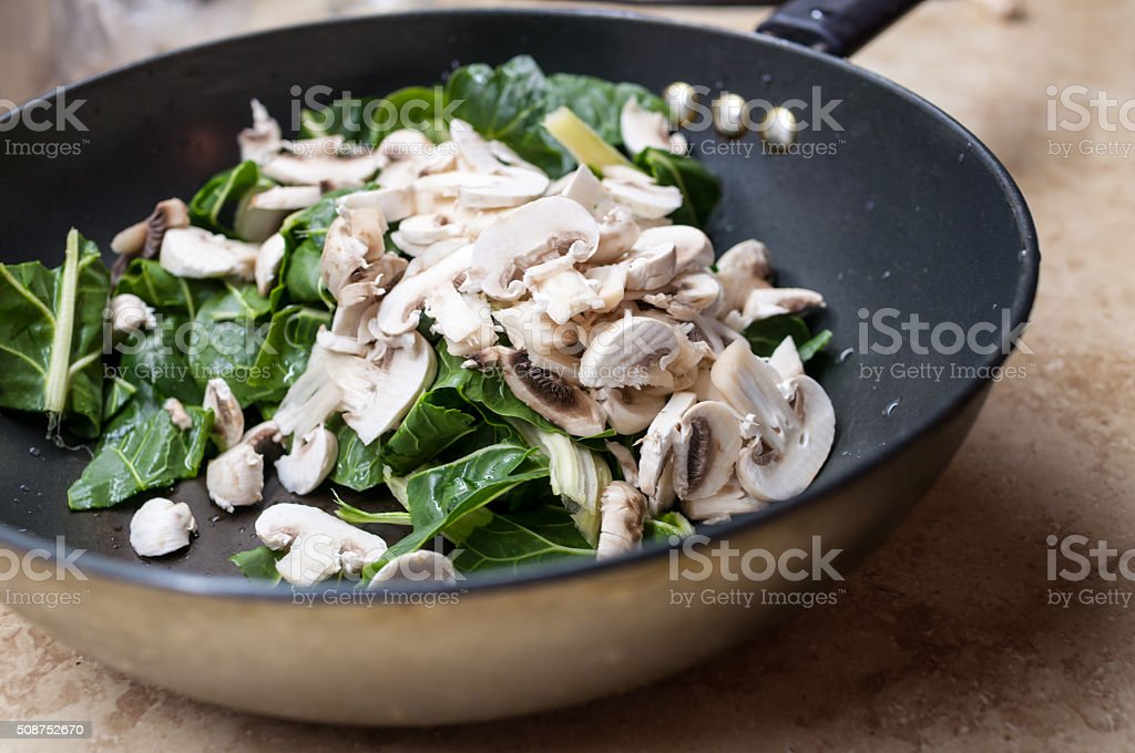 Cut spinach and mushrooms in wok stock photo