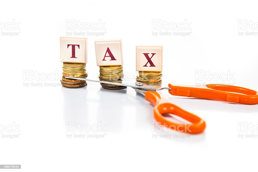 Cut taxes concept with coins and scissors stock photo