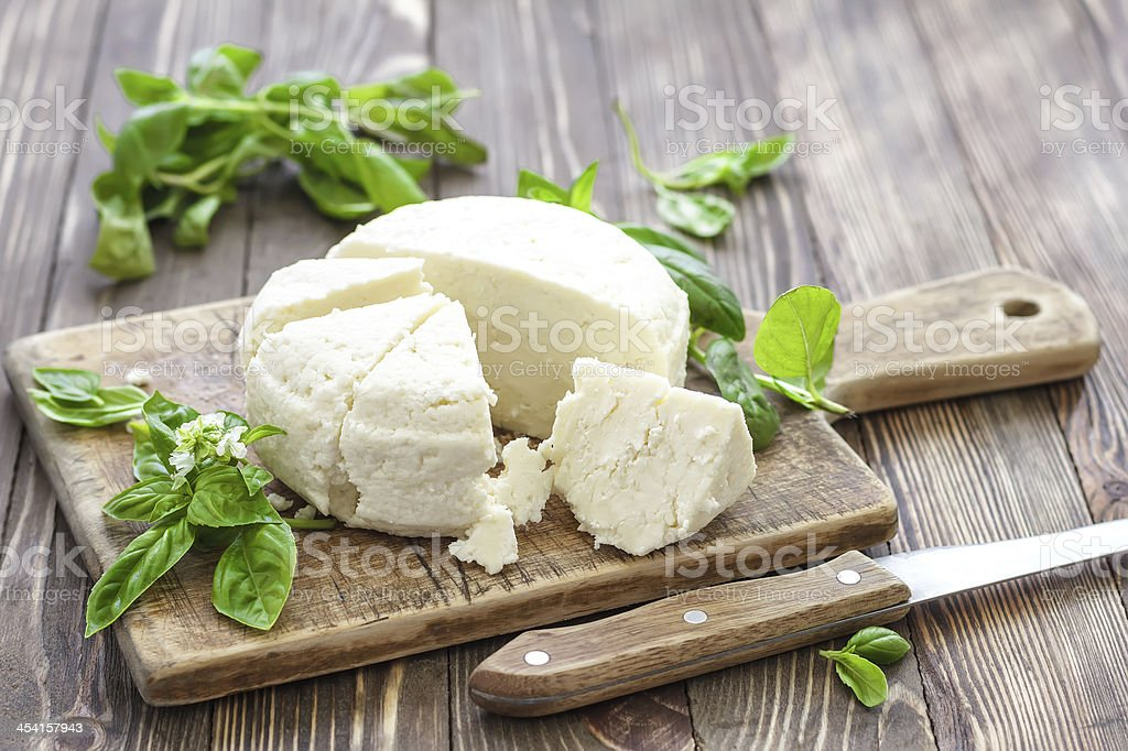 Cut up cheese on wooden board with mint leaves stock photo
