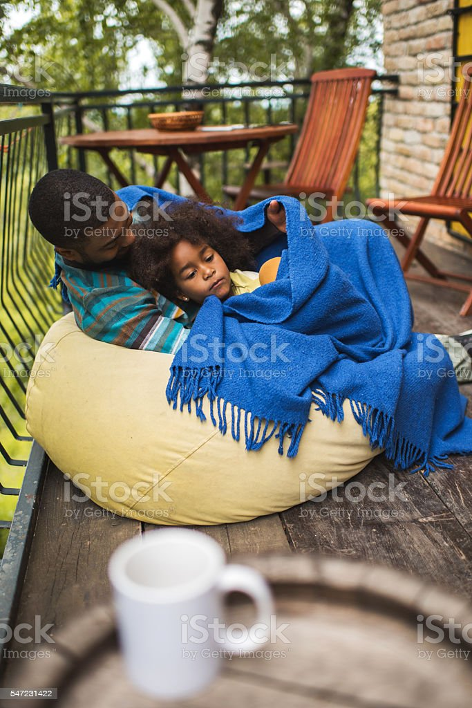 Cute African American girl relaxing with her father on terrace. stock photo
