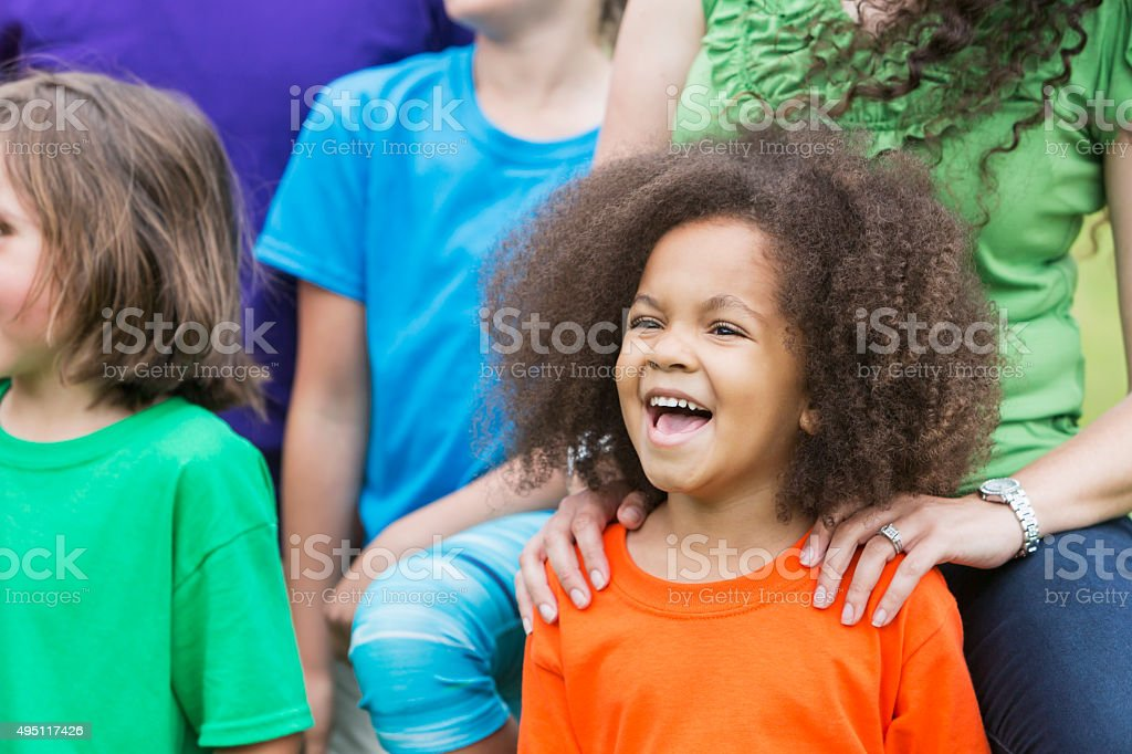 Cute African American girl shouting, standing with group stock photo