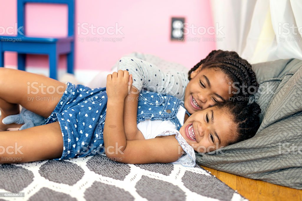 Cute African American girl tickling younger sister on the floor stock photo