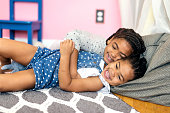 Cute African American girl tickling younger sister on the floor