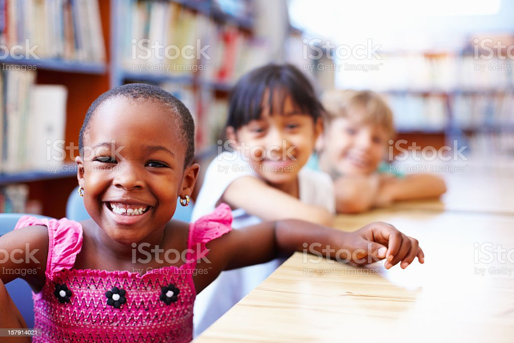 Cute African American girl with friends in the library royalty-free stock photo