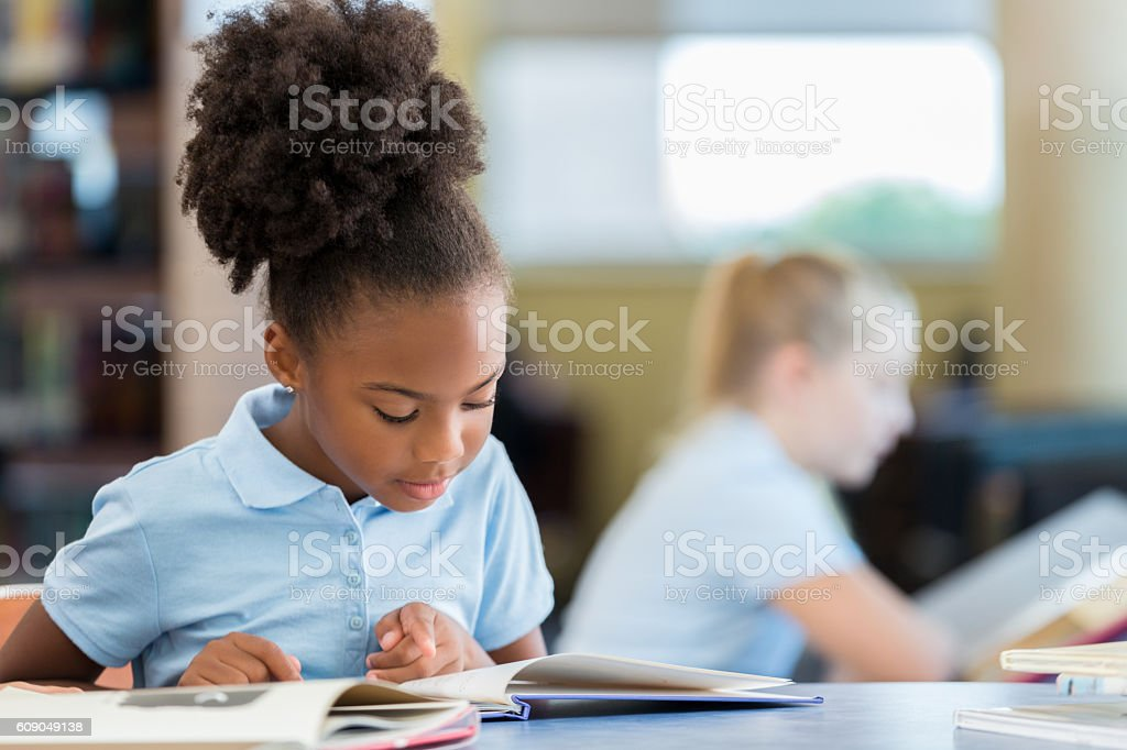 Cute African American schoolgirl reading a book in the library stock photo