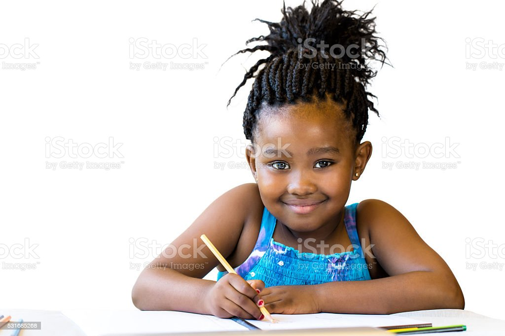 Cute african girl holding color pencil at desk. stock photo