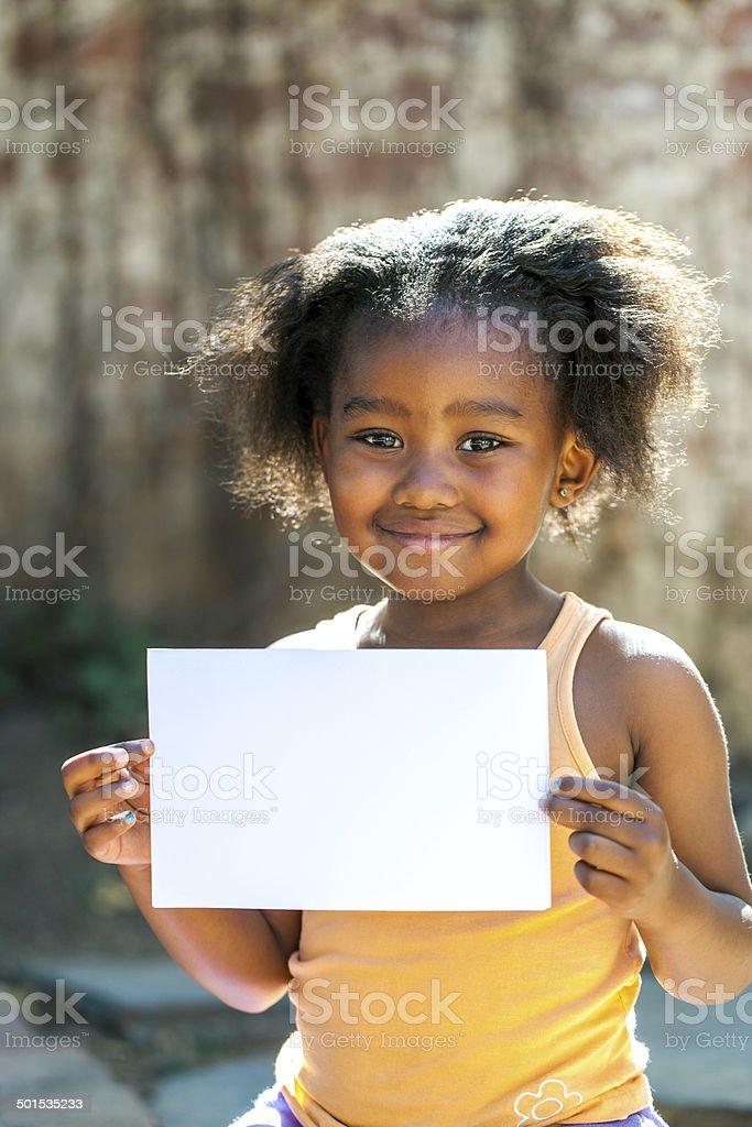 Jolie fille africaine tenant blanc carte vierge. photo libre de droits