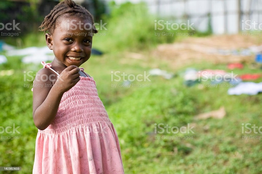 Cute African girl in pink dress smiling at camera stock photo
