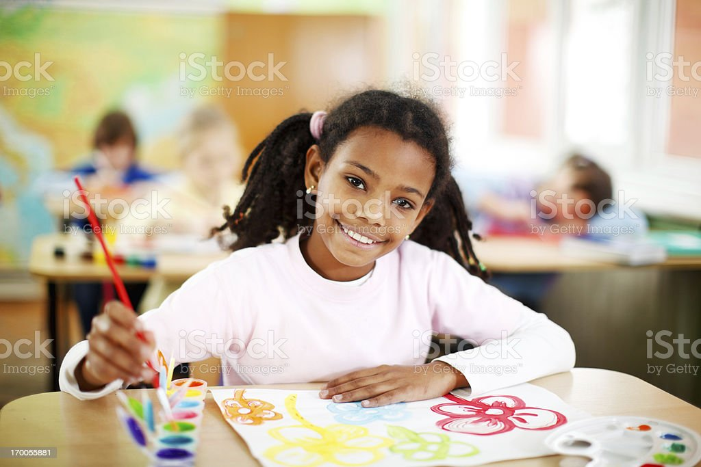 Cute African-American girl is painting with watercolors. stock photo