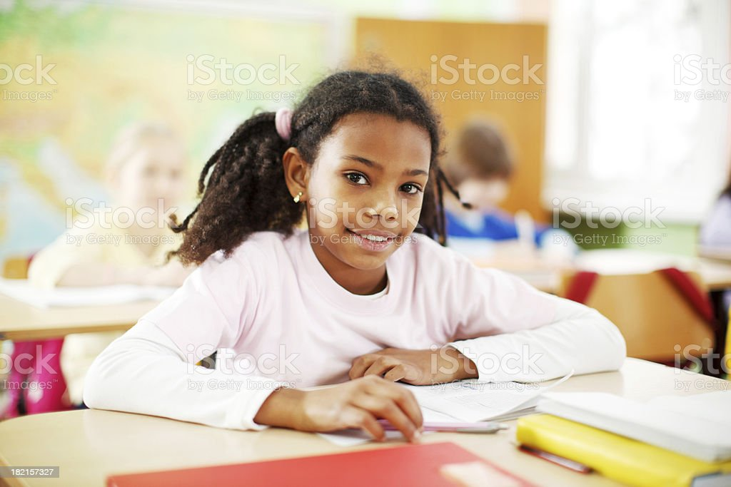 Cute African-American girl is studying in the classroom. royalty-free stock photo