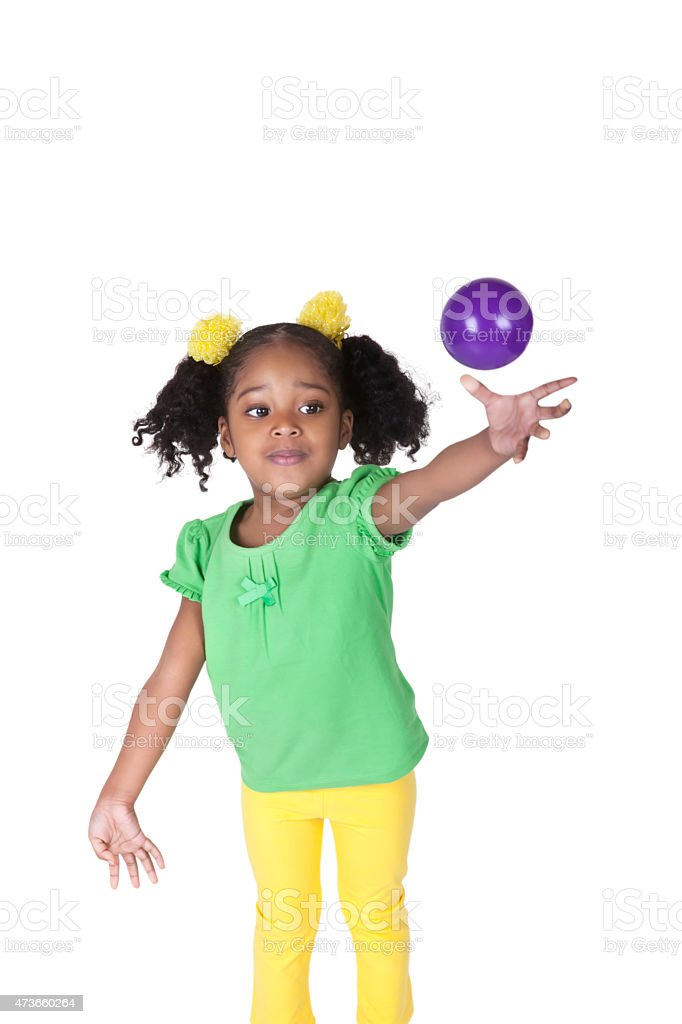 Cute Afro American four year old girl throws a ball stock photo