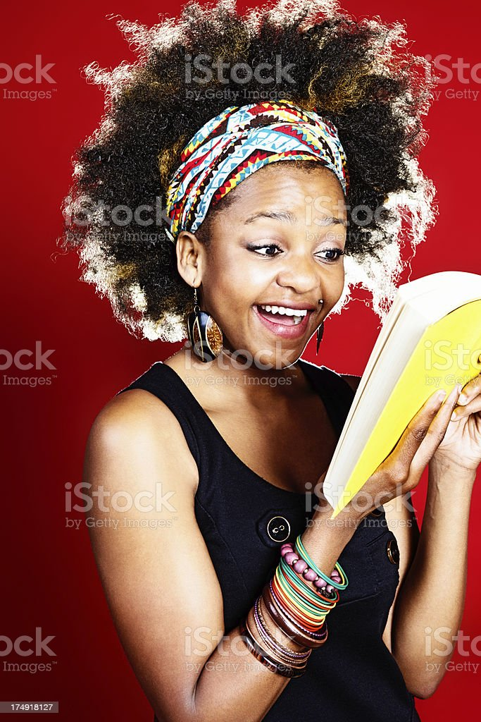 Cute afro-haired woman laughs in delight at humorous book royalty-free stock photo