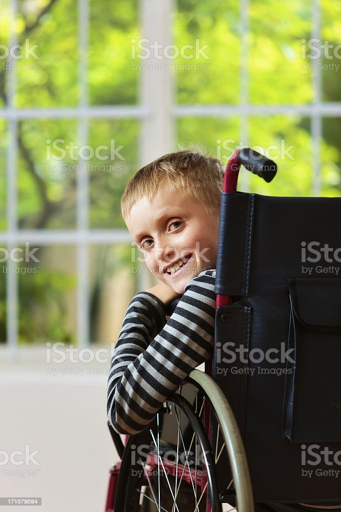 Cute, appealing blond 9-year-old in wheelchair smiles bravely stock photo