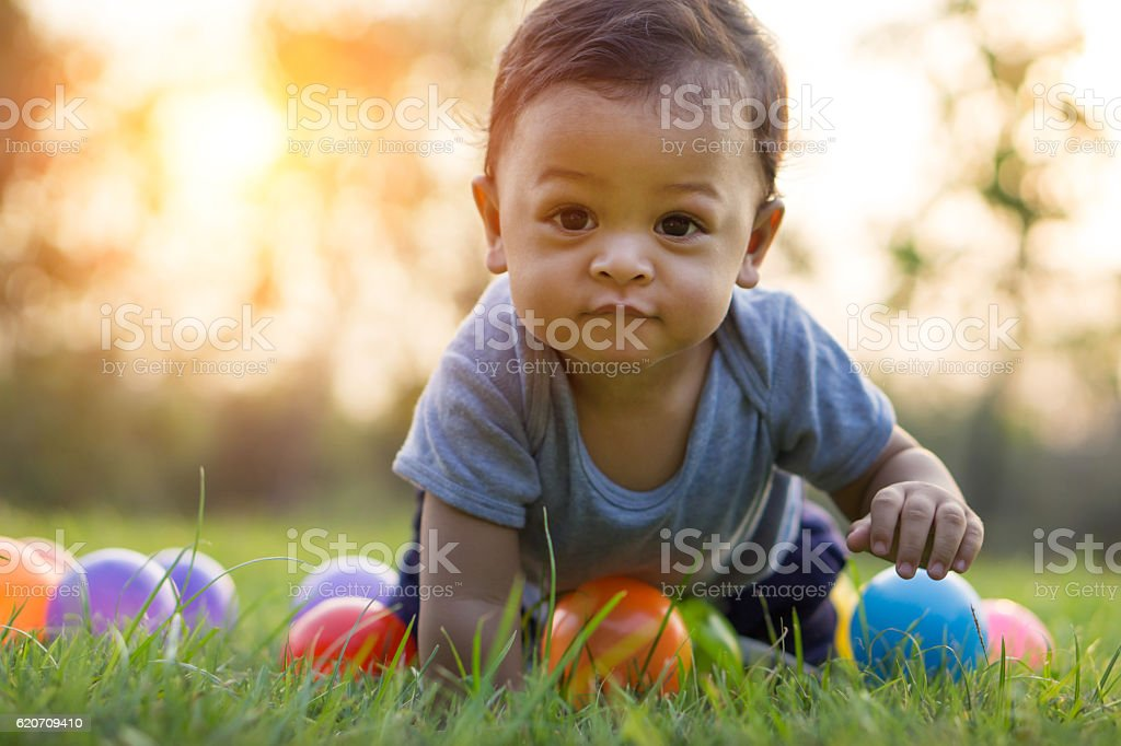 Cute asian baby crawling in the grass and colorful ball stock photo