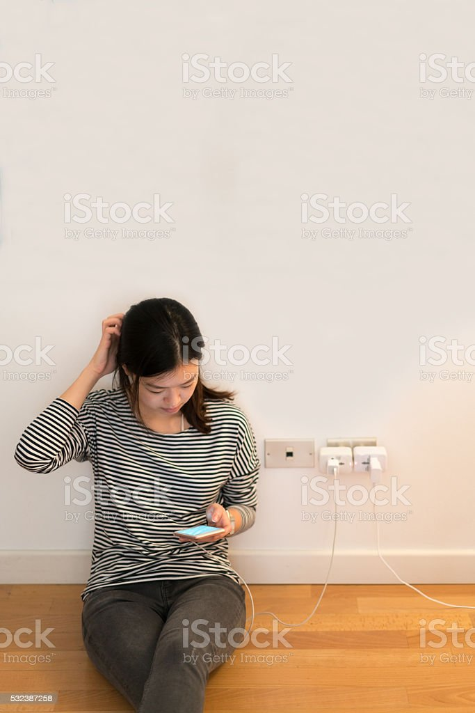 Cute asian girl frustrating with phone, charging battery, with copy space stock photo