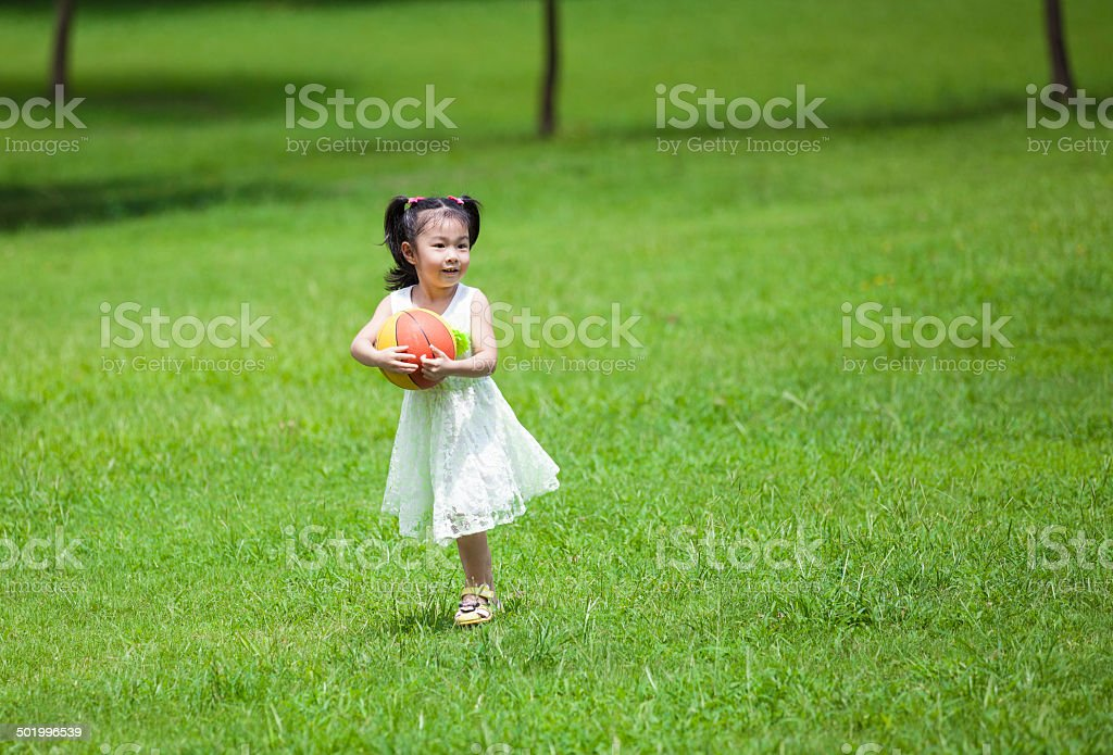 Cute Asian girl holding a ball outdoors royalty-free stock photo